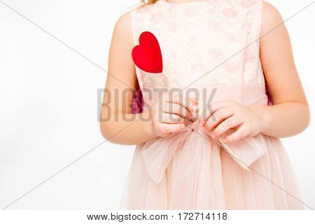 Partial view of girl in pink dress holding red paper heart on stick