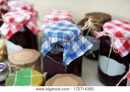 Homemade jams assortment in glass jars with plaid cloth on it, for sale on country fair. Fresh healthy organic sweet preserves