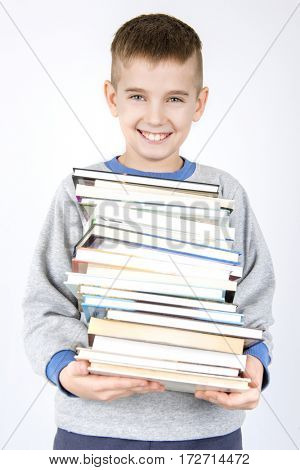 Happy smiling schoolboy holding pile of books