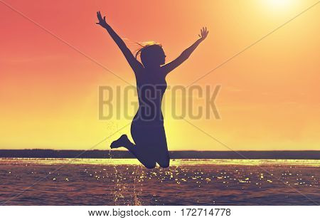 Silhouette of a beautiful slim girl who jumps on a background of a sunset on the beach.