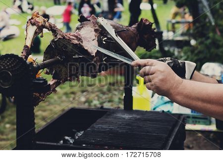 Barbecue picnic at country fair. Lamb roasted at spit. Grill, big piece of meat at rolling skewer. Street vendor, professional chef hands cooking bbq food, unrecognizable. Catering concept