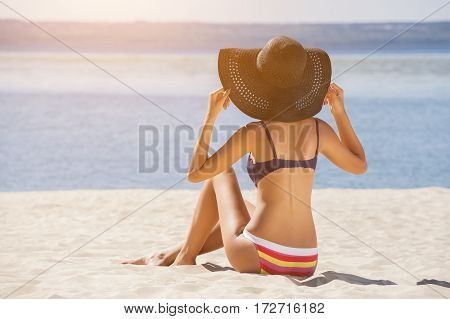 Attractive, Young Girl In A Bathing Suit Sitting On The Beach And Sunbathing On The Sunset Sky Backg