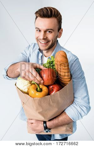 Handsome Young Man Holding Grocery Bag And Smiling At Camera