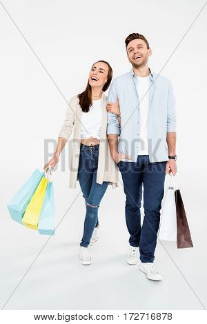 Full Length View Of Happy Young Couple Walking With Shopping Bags On White