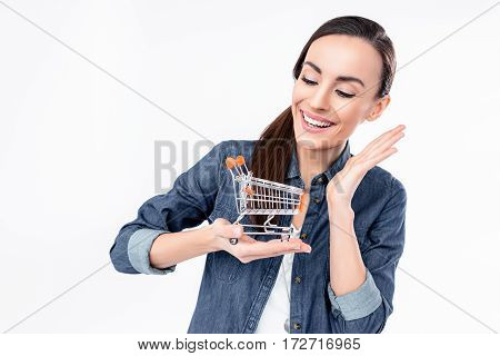 Smiling young woman holding shopping cart model on white