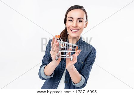 Attractive young woman holding shopping cart model and smiling at camera