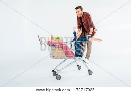 Excited young couple riding on shopping cart with grocery bag on white