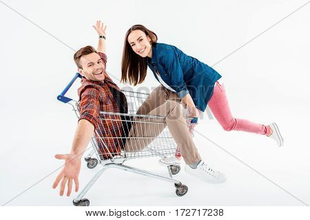 Smiling Young Woman Pushing Shopping Cart With Excited Young Man On White