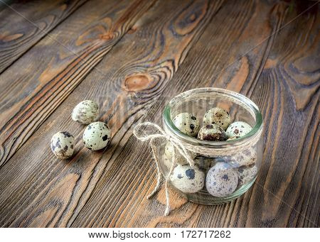 Fresh quail eggs in a glass jardecorated with a linen rope kitchen wooden table. Dark background close-up. Front view horizontal frame. Copy space