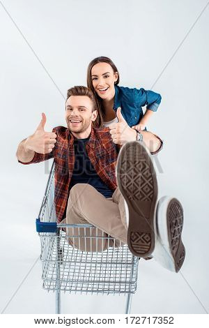 Young Woman Carrying Shopping Cart With Happy Man Showing Thumbs Up