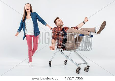 Smiling Young Woman Carrying Happy Man In Shopping Cart