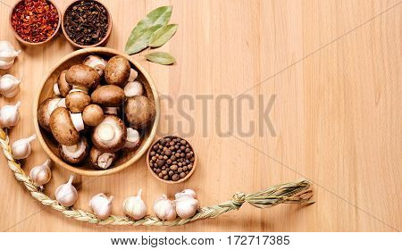 Mushrooms in wooden plate braid of garlic allspice and bay leaves on a light wooden surface. Top view.
