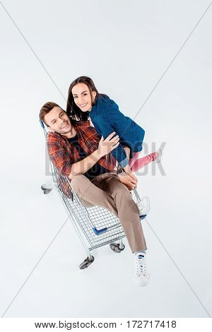 High Angle View Of Young Couple In Shopping Cart Smiling At Camera