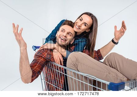 Happy Young Couple Hugging In Shopping Cart On White