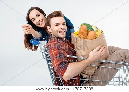 Young Man Sitting In Shopping Cart With Grocery Bag And Woman Showing Blank Card
