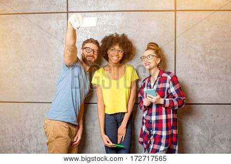 Multi ethnic coworkers dressed casually in colorful clothes making selfie photo with smart phone standing together on the gray wall background
