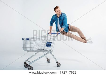 Excited young man jumping and having fun with shopping trolley on white