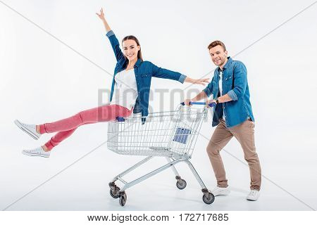 Smiling Man Pushing Shopping Cart With Happy Woman Sitting On It
