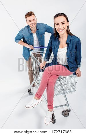 Woman Sitting On Shopping Cart With Man Looking At Her On White