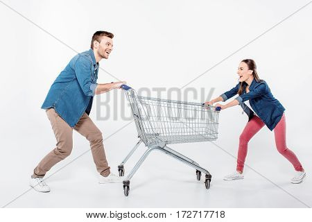 smiling couple pulling empty shopping cart and looking on each other on white