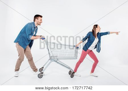 woman pointing way and while pulling shopping cart with man on white