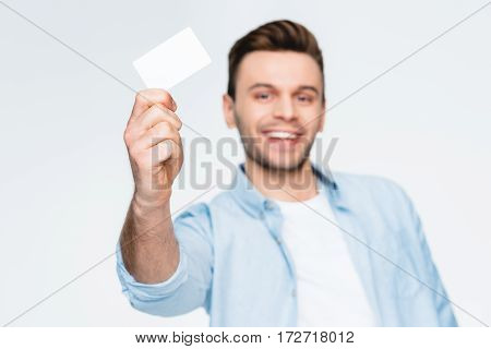 portrait of smiling man showing credit card and looking to camera focus on foreground