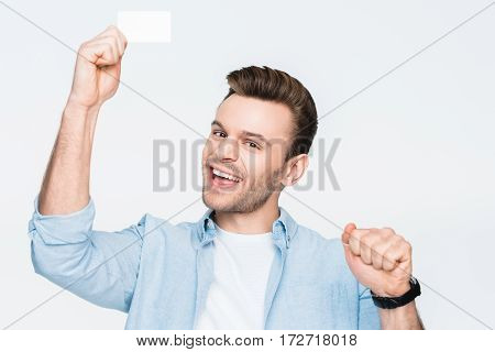portrait of happy man holding credit card in hand and looking to camera