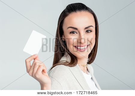 portrait of smiling woman holding credit card in hand and looking to camera