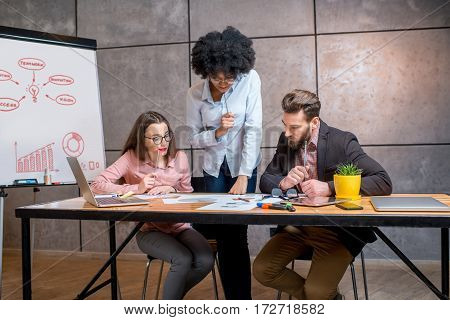 Multi ethnic coworkers working together with documents and laptop at the workplace with whiteboard on the grey wall background