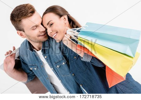 Portrait Of Smiling Couple Holding Shopping Bags And Looking Away On White