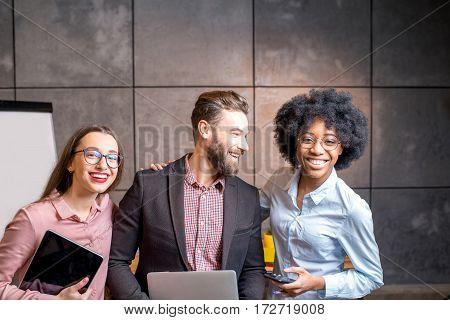 Portrait of three happy multi ethnic coworkers together at the office
