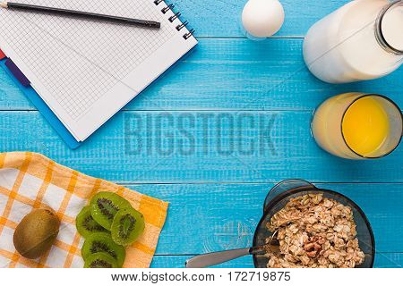 Breakfast table with granola, milk, fruits and juice. Top view. Space for text. Still life