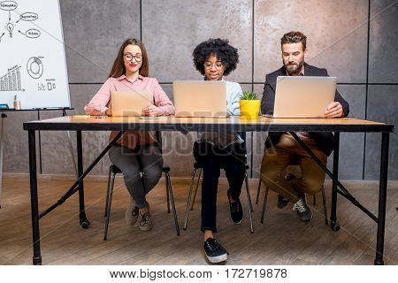 Multi ethnic coworkers working together with laptops and whiteboard at the modern office interior on the grey wall background