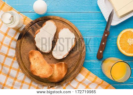 Breakfast table with bread, milk butter, fruits and juice. Top view. Still life