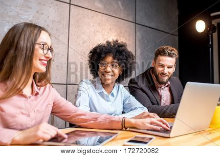 Multi ethnic coworkers working together with gadgets at the modern office interior on the grey wall background