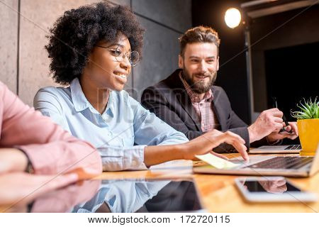 Beautiful african woman with handsome caucasian man working with laptop at the modern office interior