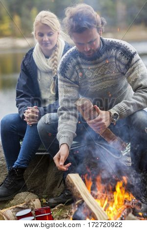 Couple Sitting By Bonfire On Lakeshore