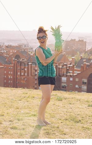 full body of a joyfull young girl smilling holding a pineapple with glasses.