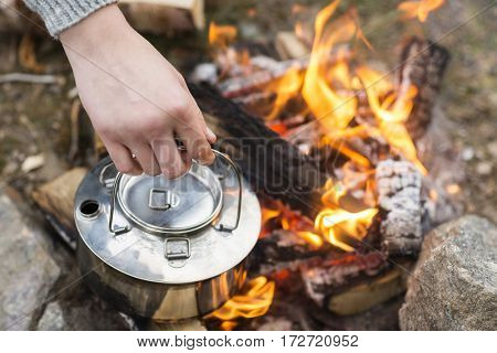 Closeup Of Hand Holding Kettle Over Bonfire