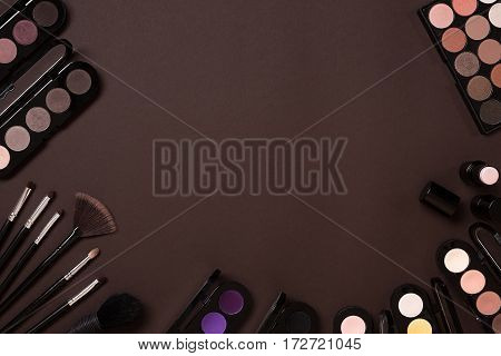 Colorful cosmetics on brown workplace with copy space. Cosmetics make up artist objects: lipstick, eye shadows, powder, tools for make-up.Top view selective focus.