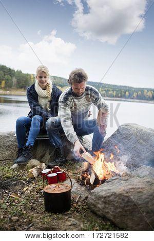 Hiking Couple Preparing Bonfire On Lakeshore