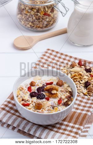 Bowl of homemade muesli with nuts, berries, dried fruits, milk and honey on white wooden background. Healthy breakfast. top view