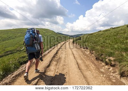 Hiker climbing up mountain in summer sunny day