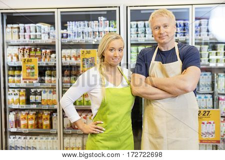 Male And Female Workers Standing In  Grocery Store