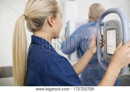 Female Professional Taking Xray Of Male Patient