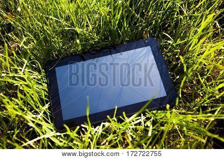 Tablet Computer on the Green Grass closeup