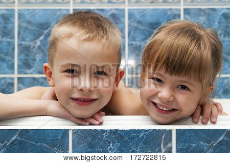 Brother and sister taking a bubble bath. Little boy and girl playing. Healthcare and hygiene concept.