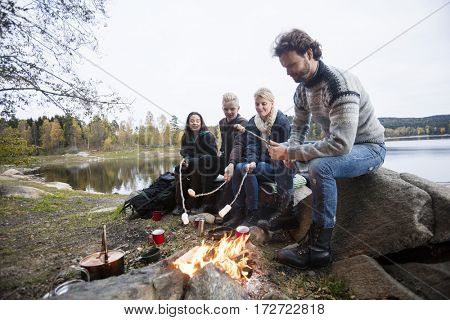 Friends Roasting Marshmallows Over Campfire At Lakeshore