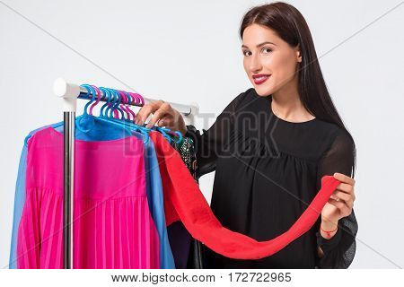 Happy woman shopping and choosing clothes isolated on a white background. Beautiful brunette chooses dress