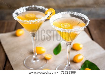 cocktail with kumquat on wooden background close up